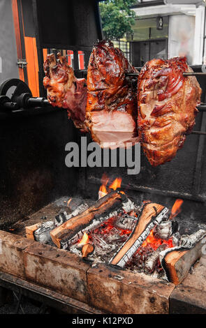 A spit for cooking roast shank in Prague on a Sunny day. National cuisine. The street food. - Stock Photo