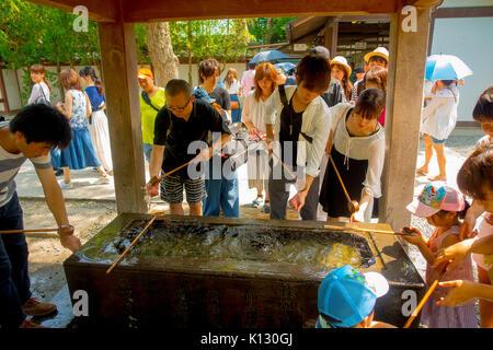 TOKYO, JAPAN JUNE 28 - 2017: Unidentified people at Kotokuin Temple in Kamakura, Japan, wash basin and dippers for - Stock Photo