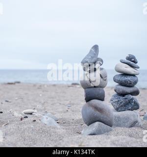 Monochrome, Serene, Blue Stacked rocks on a California beach symbolizing Peace, Balance, Meditation, and Mindfulness - Stock Photo