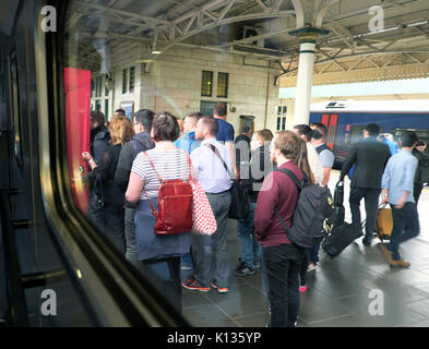 Commuters waiting to board an intercity train carriage going between London Paddington and Swansea at Cardiff Central - Stock Photo