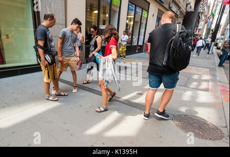 Tourists stop to look at a plaque commemorating French Field Marshal Philippe Pétain embedded in the Canyon Of Heroes - Stock Photo
