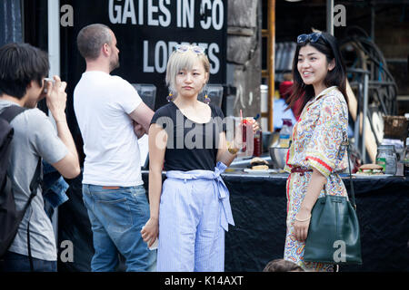 London, UK - August 17, 2017: Columbia Road Flower Sunday market. Two girls posing with a cocktail in hand - Stock Photo