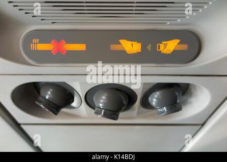 Passenger No Smoking Fasten Seat belt sign & cool air nozzles / nozzle array / vents. Airbus A320 aircraft / air - Stock Photo
