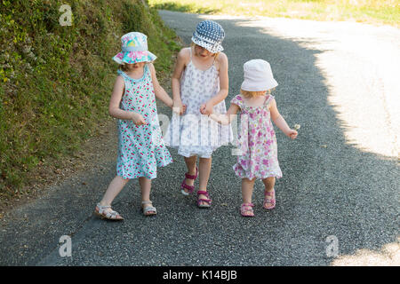 Three young French girls, sisters, walk hand-in-hand holding hands along a French country road in the summer. They - Stock Photo