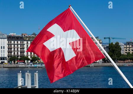 The Swiss flag, flag of Switzerland, flying over Lake Geneva / Lac Léman. Geneva / Geneve, Switzerland. - Stock Photo