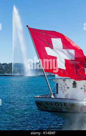 The Swiss flag, flag of Switzerland, flying over the lake in front of Jet d'Eau tall fountain on Lake Geneva / Lac - Stock Photo