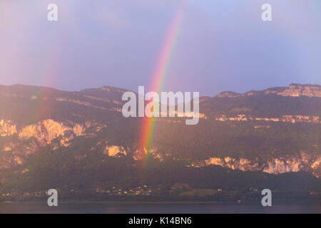 View – with rainbow – across Lac Du Bourget from Conjux to ridge between Col Du Sapenay and La Chambotte & the mountainside - Stock Photo
