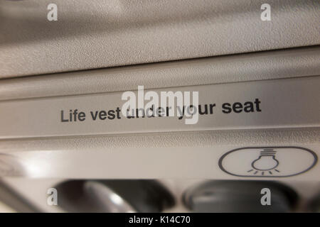 Safety warning information regarding life vest / life jacket being under the aircraft seat. (89) - Stock Photo