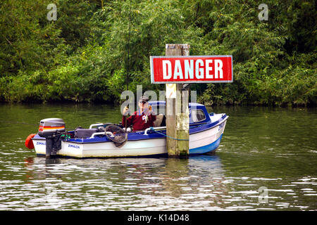 Man fishing in a small motorboat moored in the middle of the river Thames tied to a wooden post saying danger - Stock Photo