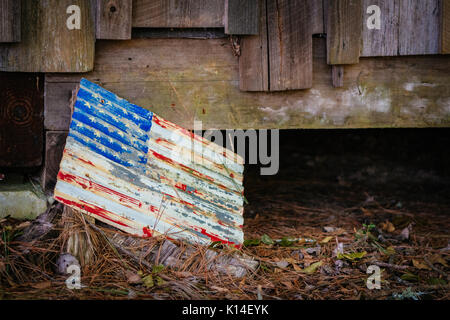 American flag painted on an old sheet of metal, weathered, found on the ground by an abandoned cabin in central - Stock Photo