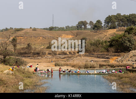 Women washing clothes in river, Meghalaya, India - Stock Photo