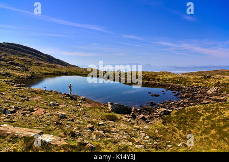 Small lake in the mountains with hiker standing on the rocky shore, Applecross, Wester Ross, Scotland - Stock Photo