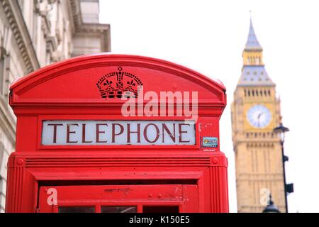 retro red phone box in London with  big ben in the background - Stock Photo