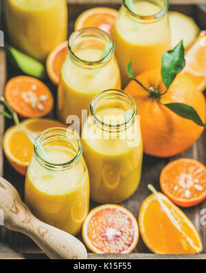 Healthy yellow smoothie in bottles with fresh fruits - Stock Photo