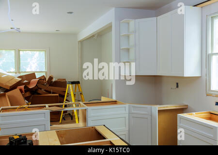Custom kitchen cabinets in various stages of installation - Stock Photo