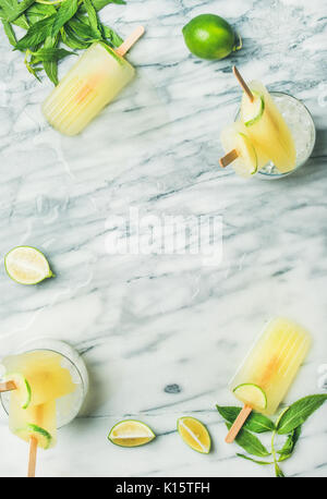 Summer refreshing lemonade popsicles with lime and mint leaves - Stock Photo