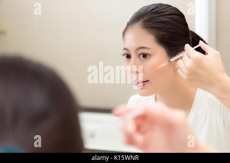 closeup portrait of young woman using syringe injection cosmetic care product standing in front of bathroom mirror - Stock Photo