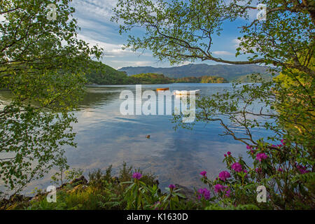 Stunning landscape with Loch Morar hemmed with rugged mountains and with boats on calm blue water under blue sky - Stock Photo