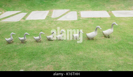 Ceramic ducks decoration sculpture on green grass - Stock Photo