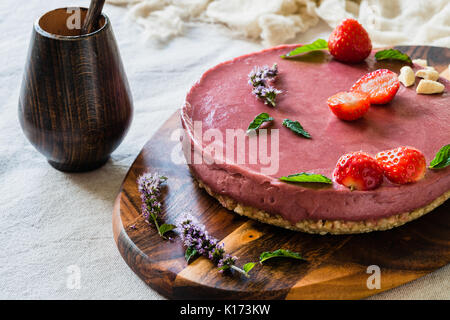 Raw healthy vegan cheesecake, homemade with cashew, mint and strawberries - Stock Photo