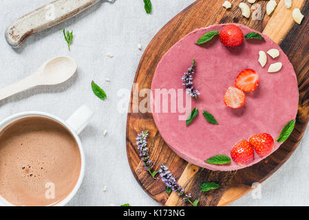 Raw healthy cheesecake, homemade with mint and strawberries. Breakfast table with hot drink. Top view - Stock Photo