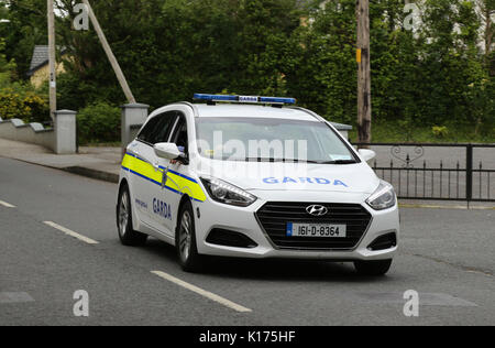 A patrol car of the Irish police, the Garda, driving near Kenmare town, County Kerry, Ireland. - Stock Photo