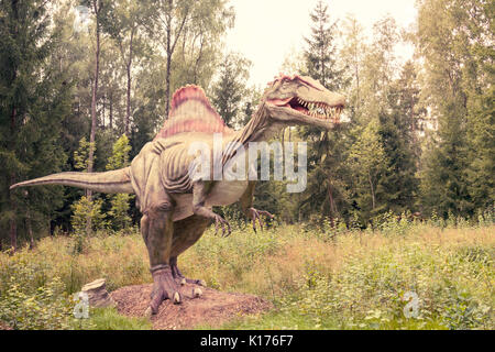 Statue of Spinosaurus dinosaur in a green forest - Stock Photo