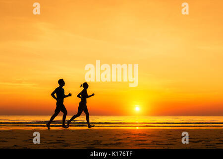 Silhouette of active sporty couple running on the beach at sunset - Stock Photo