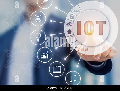 Internet of Things technology with connected objects, hand touching button with text IOT on AR (Augmented Reality) - Stock Photo