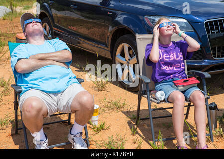 Observers wearing eclipse glasses watch the Great American Eclipse on August 21, 2017. - Stock Photo