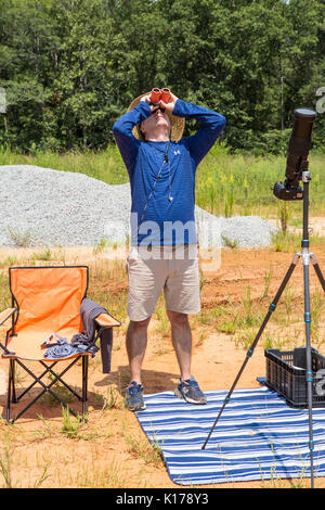 A photographer with solar binoculars observes the Great American Eclipse on August 21, 2017. - Stock Photo