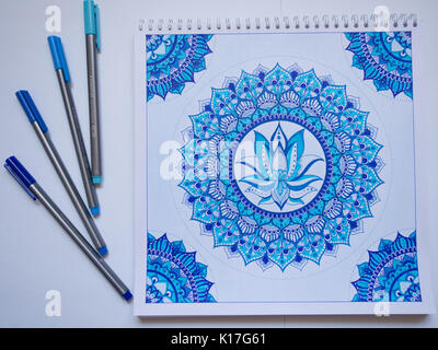 Concept photo of the pens and a sketchbook with a picture of a blue handmade mandala - Stock Photo