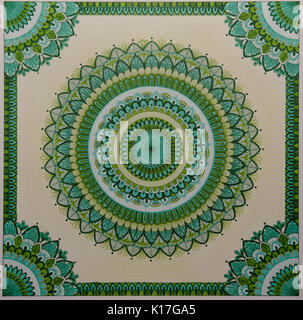 Photo of a sketchbook with a picture of a green handmade  mandala - Stock Photo