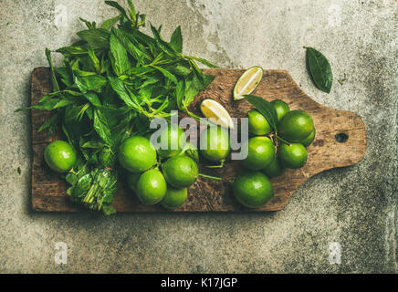 Flatlay of fresh limes and mint on wooden board - Stock Photo
