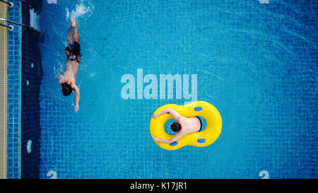Top view, a man relaxing on yellow swim pool float, on swimming pool in summer - Stock Photo