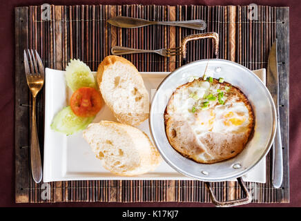 Breakfast meal, fried eggs pan and breads on the table - Stock Photo