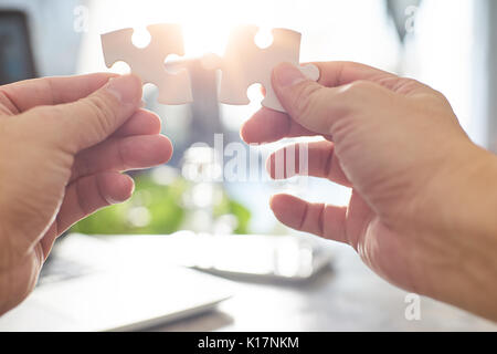 Young businessman trying to connect couple puzzle piece with sun flare and blur background,symbol of association - Stock Photo