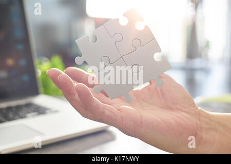 Young businessman showing puzzle partnership puzzle piece with sun flare and blur background,symbol of association - Stock Photo