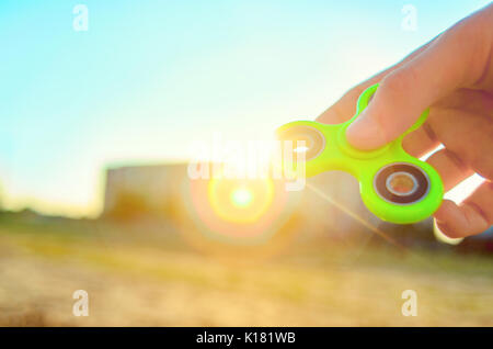 Teenager hand holding  trendy antistress gadget fidget spinner. Man playing with green spinner outdoors on the bright - Stock Photo