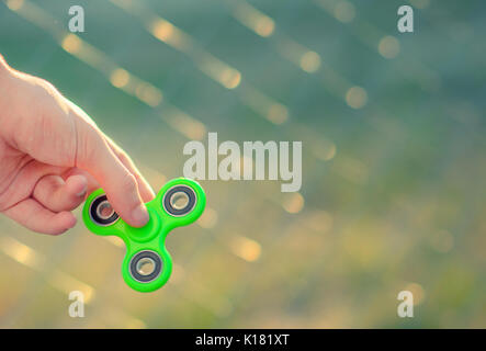 Young man hand holding antistress modern gadget fidget spinner. Teenager playing with green spinner outdoors on - Stock Photo