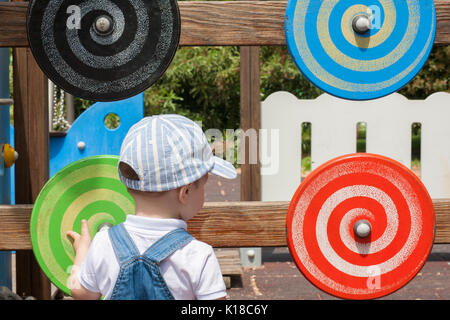 2 year-old boy playing with wooden colored disc with spiral draw in motion. Playground toy - Stock Photo