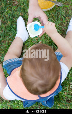 2 year-old boy eating a yoghurt sitting on the grass. He is been helped by his mother - Stock Photo