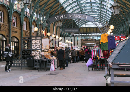 LONDON, UK - February 10: Famous Apple Market inside Covent Garden with people walking around and shopping in London, - Stock Photo
