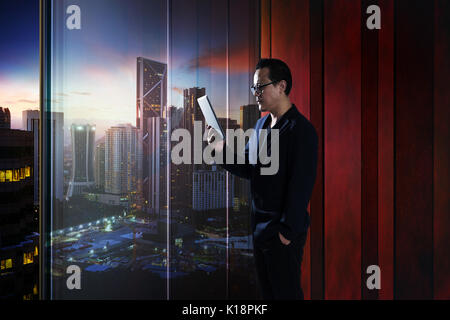 Young asian businessman holding and using digital tablet . evening scene . - Stock Photo