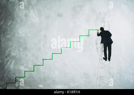 Men drawing stair on grey wall . - Stock Photo