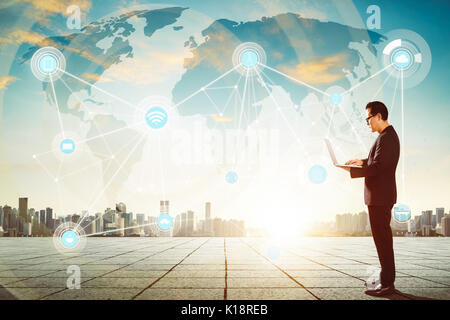 Businessman using laptop with smart city and wireless communication network background , evening scene . - Stock Photo