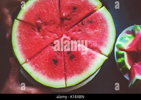 A man cuts a ripe red watermelon. Slices of watermelon closeup - Stock Photo