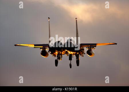 McDonnell Douglas Boeing F-15E Strike Eagle landing at RAF Lakenheath in Suffolk at sunset - Stock Photo
