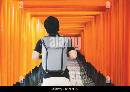 Asian traveler man with backpack standing at Red Tori Gate at Fushimi Inari Shrine in Kyoto, Japan. - Stock Photo