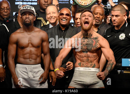Las Vegas NV, USA. 25th Aug, 2017. (L-R) Floyd Mayweather Jr. poses off with Conor McGregor during todays weigh - Stock Photo